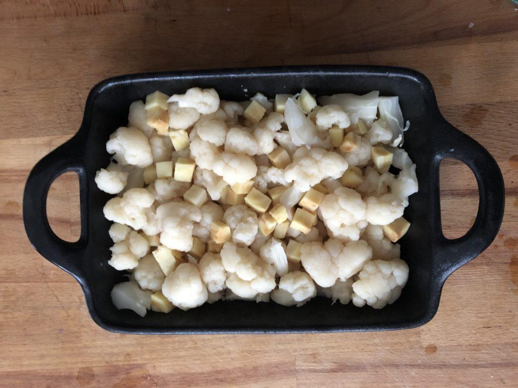 Répartition des légumes cuits à la vapeur dans le plat à gratin.
